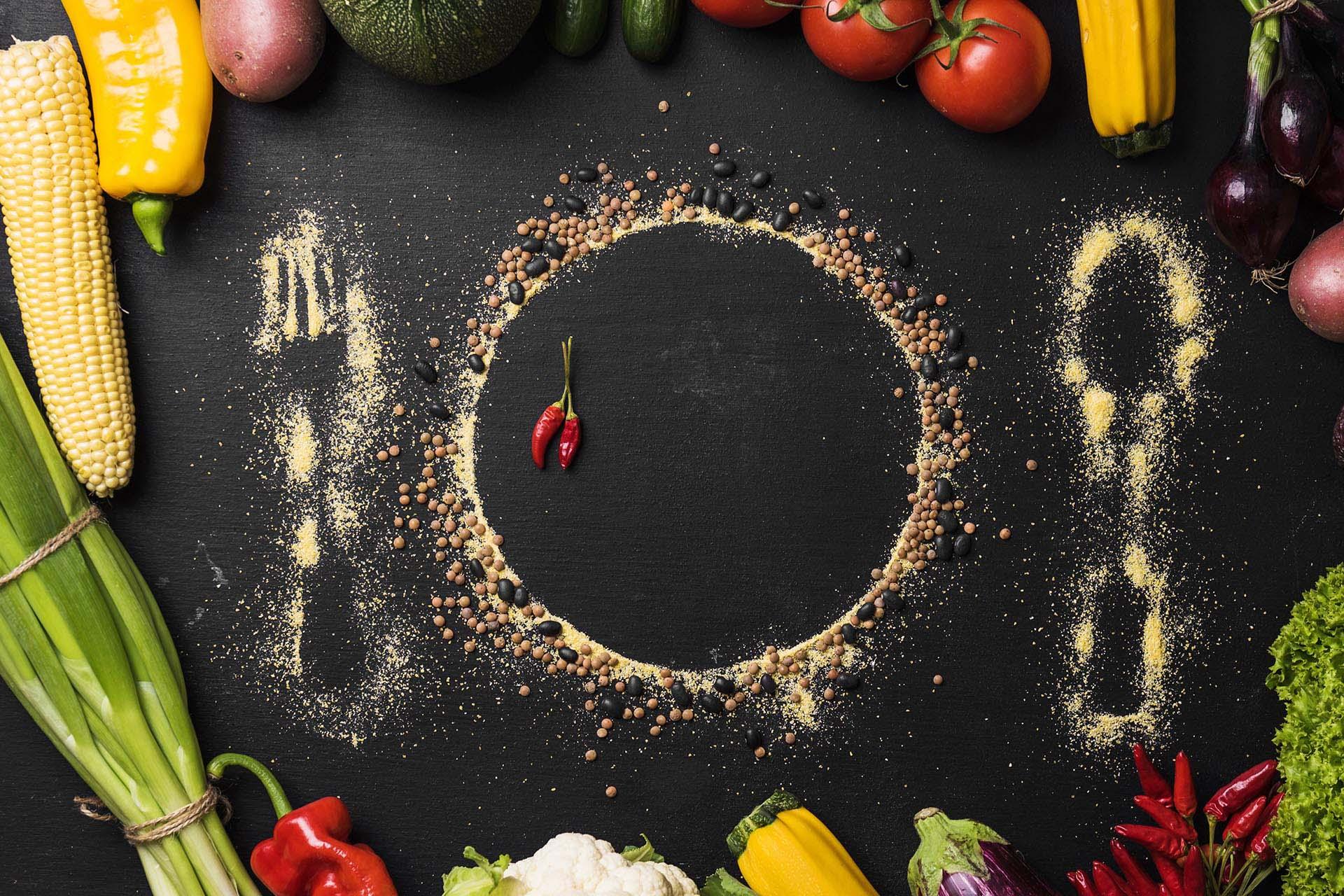 Cuisine-Lifestyle - Gemüse mit einem Umriss von Teller und Besteck auf schwarzem Grund